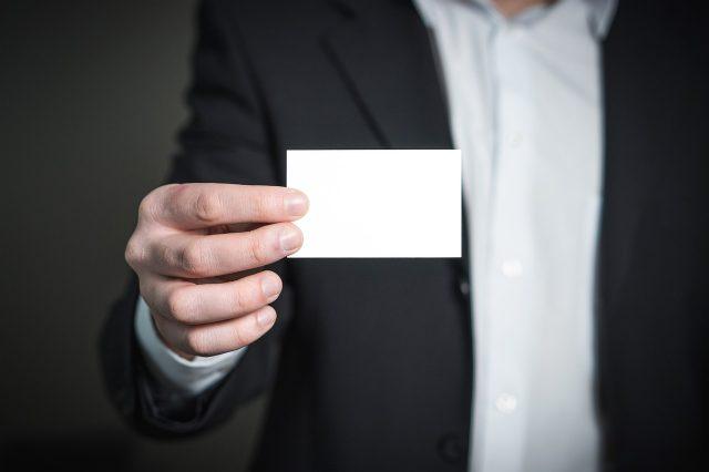 名刺大の白いカードを持つ男性